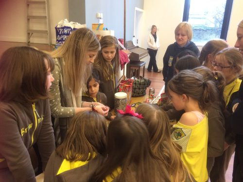 Brooke teaching Girl Guides how to make ring pull bracelets.